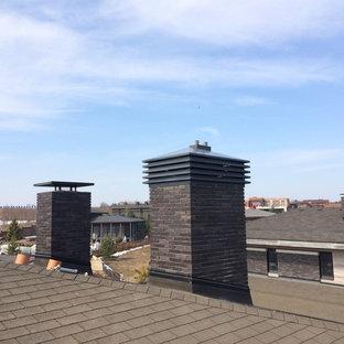 Modelo de fachada de casa negra, urbana, grande, a niveles, con revestimiento de ladrillo, tejado a cuatro aguas y tejado de teja de madera