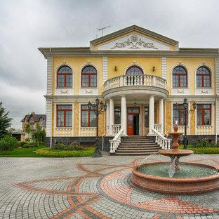 Идея дизайна: двухэтажный, желтый частный загородный дом в классическом стиле
