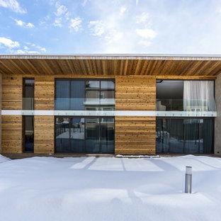 Удачное сочетание для дизайна помещения: двухэтажный фасад дома коричневого цвета в современном стиле с облицовкой из дерева и плоской крышей - самое интересное для вас