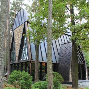 На фото: двухэтажный частный загородный дом в современном стиле с двускатной крышей и металлической крышей с