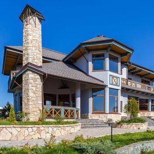 Пример оригинального дизайна: большой, трехэтажный, серый частный загородный дом в стиле кантри с облицовкой из камня, вальмовой крышей и крышей из гибкой черепицы