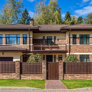 На фото: двухэтажный, коричневый частный загородный дом в современном стиле с комбинированной облицовкой, вальмовой крышей и черепичной крышей с
