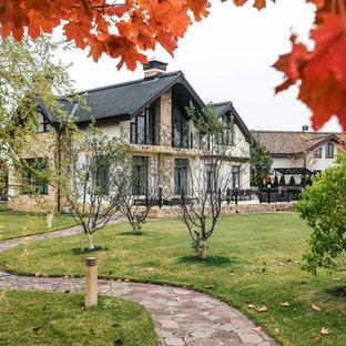 На фото: двухэтажный фасад дома бежевого цвета в стиле кантри с двускатной крышей с
