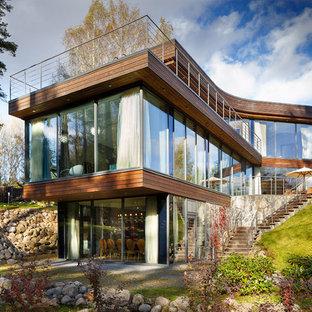 Идея дизайна: коричневый частный загородный дом в современном стиле с разными уровнями и плоской крышей