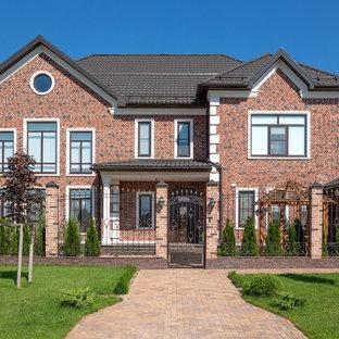 Свежая идея для дизайна: двухэтажный фасад частного дома коричневого цвета в классическом стиле с облицовкой из кирпича и двускатной крышей - отличное фото интерьера