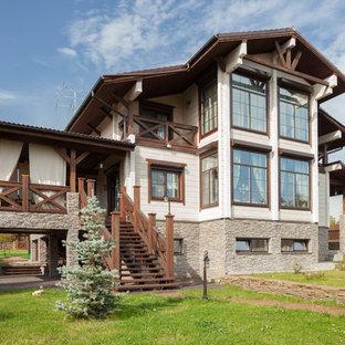 На фото: двухэтажный частный загородный дом в классическом стиле с двускатной крышей