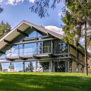 Пример оригинального дизайна: двухэтажный, стеклянный, белый частный загородный дом в современном стиле с двускатной крышей