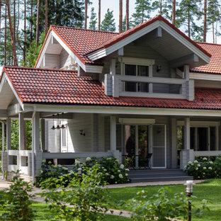 Inspiration för ett funkis grått hus, med två våningar och sadeltak