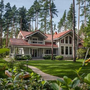Пример оригинального дизайна: двухэтажный, деревянный, серый частный загородный дом в современном стиле с двускатной крышей и коричневой крышей