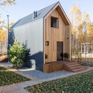 На фото: маленький, двухэтажный, деревянный, коричневый частный загородный дом в скандинавском стиле с двускатной крышей и металлической крышей с
