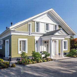 Выдающиеся фото от архитекторов и дизайнеров интерьера: двухэтажный фасад частного дома зеленого цвета в классическом стиле с облицовкой из дерева и двускатной крышей
