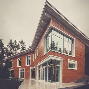 Imagen de fachada de casa naranja, actual, de tamaño medio, de dos plantas, con revestimiento de madera, tejado de un solo tendido y tejado de teja de madera