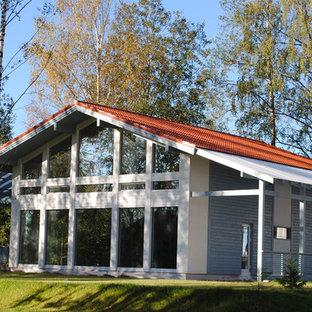 Ejemplo de fachada de casa escandinava, de tamaño medio, de dos plantas, con revestimiento de vidrio, tejado a dos aguas y tejado de teja de barro