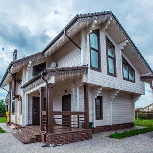 Стильный дизайн: двухэтажный, деревянный, бежевый частный загородный дом в стиле современная классика с двускатной крышей - последний тренд
