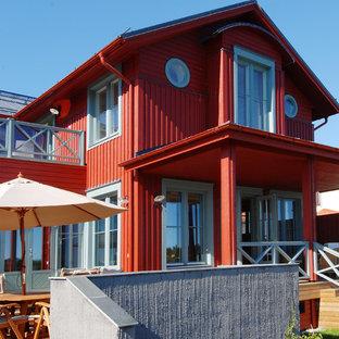 Новый формат декора квартиры: двухэтажный фасад частного дома красного цвета в морском стиле с облицовкой из дерева, двускатной крышей и металлической крышей