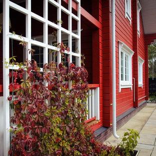 Идея дизайна: двухэтажный, деревянный, красный частный загородный дом в стиле кантри