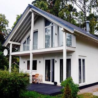 Imagen de fachada de casa blanca, escandinava, pequeña, de dos plantas, con revestimientos combinados, tejado a dos aguas y tejado de teja de barro