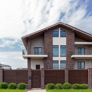 Foto della villa marrone contemporanea con tetto a capanna