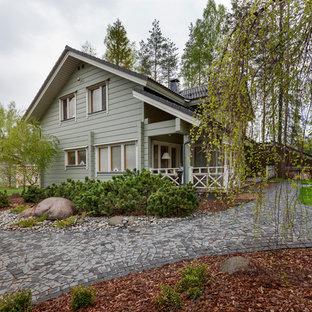 Пример оригинального дизайна: двухэтажный фасад частного дома серого цвета в классическом стиле с облицовкой из дерева и двускатной крышей
