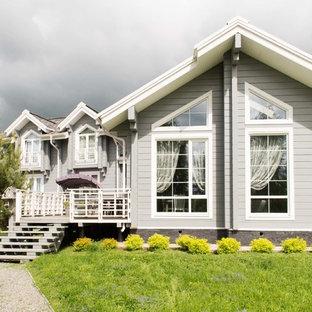 На фото: двухэтажный, деревянный, серый частный загородный дом в классическом стиле с двускатной крышей с