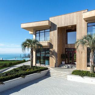 Идея дизайна: двухэтажный, бежевый частный загородный дом в современном стиле с плоской крышей и облицовкой из камня