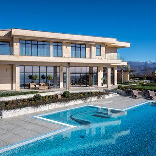 На фото: двухэтажный, бежевый частный загородный дом в современном стиле с облицовкой из камня и плоской крышей с