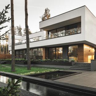 Стильный дизайн: большой, двухэтажный, разноцветный частный загородный дом в современном стиле с комбинированной облицовкой и плоской крышей - последний тренд