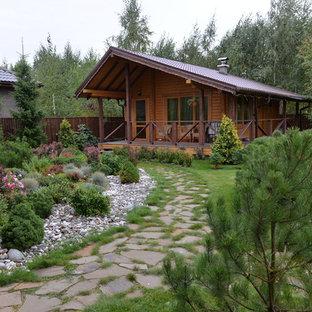 На фото: одноэтажные, деревянные, коричневые частные загородные дома в стиле рустика с двускатной крышей и черепичной крышей