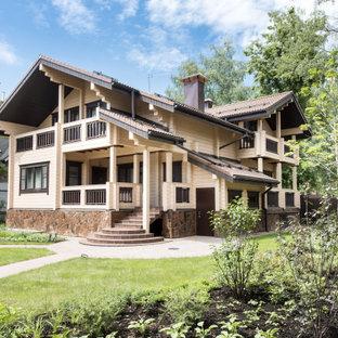 На фото: двухэтажный, деревянный, бежевый частный загородный дом среднего размера в стиле рустика с двускатной крышей с