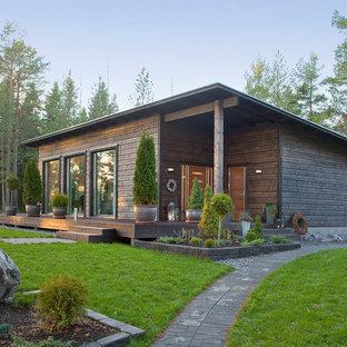 Пример оригинального дизайна: одноэтажный, деревянный, коричневый частный загородный дом среднего размера в стиле рустика с односкатной крышей