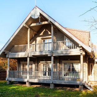 Неиссякаемый источник вдохновения для домашнего уюта: двухэтажный фасад частного дома среднего размера бежевого цвета в стиле рустика с облицовкой из дерева, двускатной крышей и крышей из гибкой черепицы