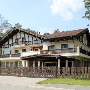 На фото: большой, трехэтажный, белый дом в стиле современная классика с двускатной крышей с
