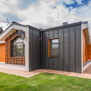 Idéer för mellanstora funkis flerfärgade hus, med allt i ett plan, sadeltak och tak i metall
