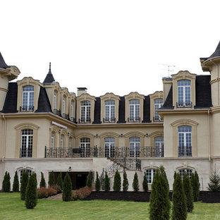 На фото: бежевый частный загородный дом в классическом стиле