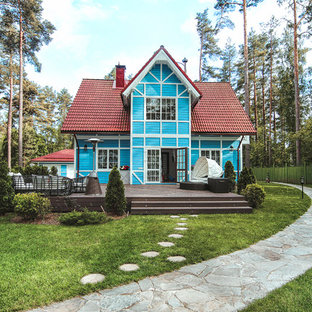 Стильный дизайн: двухэтажный, деревянный, синий частный загородный дом в стиле кантри с двускатной крышей - последний тренд