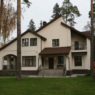 На фото: двухэтажный, бежевый дом в современном стиле с