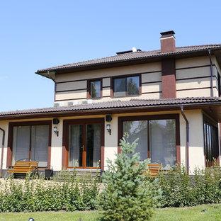 Стильный дизайн: двухэтажный, бежевый частный загородный дом в стиле современная классика - последний тренд