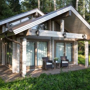 Imagen de fachada beige, escandinava, de una planta, con revestimiento de madera y tejado a dos aguas