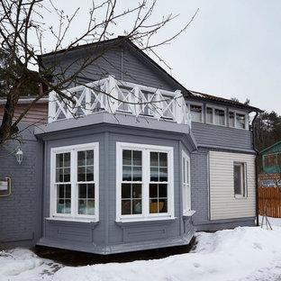 На фото: двухэтажные фасады домов серого цвета в скандинавском стиле с двускатной крышей и комбинированной облицовкой