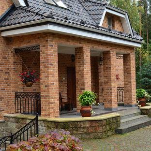 Выдающиеся фото от архитекторов и дизайнеров интерьера: большой фасад частного дома коричневого цвета в классическом стиле с облицовкой из кирпича