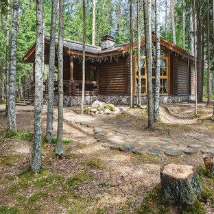 Пример оригинального дизайна: одноэтажный, деревянный, коричневый частный загородный дом в стиле рустика с двускатной крышей