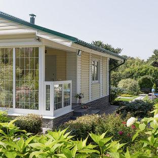 На фото: желтый дом в современном стиле с металлической крышей с