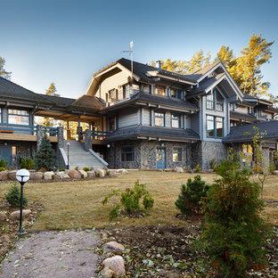 Создайте стильный интерьер: трехэтажный фасад дома серого цвета в стиле кантри с облицовкой из дерева и полувальмовой крышей - последний тренд