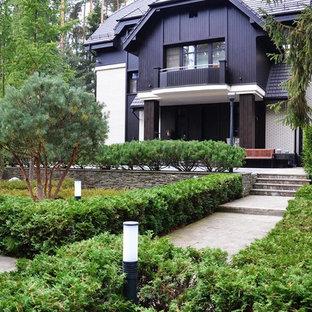 Imagen de fachada de casa negra, contemporánea, con revestimiento de madera, tejado a doble faldón y tejado de metal