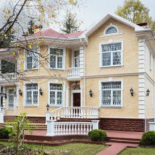 Новые идеи обустройства дома: двухэтажный фасад дома желтого цвета в классическом стиле
