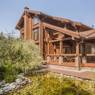 Modelo de fachada de casa marrón, escandinava, grande, de tres plantas, con revestimiento de madera, tejado a dos aguas y tejado de teja de barro
