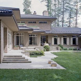 Новые идеи обустройства дома: двухэтажный фасад частного дома бежевого цвета в классическом стиле с облицовкой из кирпича, вальмовой крышей и черепичной крышей