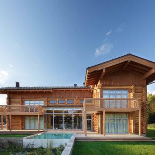 На фото: двухэтажный, деревянный дом из бревен в стиле рустика с двускатной крышей и черепичной крышей