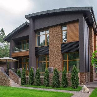 Идея дизайна: двухэтажный частный загородный дом в современном стиле с комбинированной облицовкой