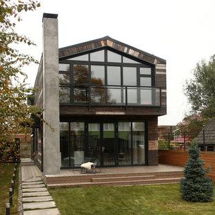 Идея дизайна: двухэтажный, коричневый, деревянный частный загородный дом среднего размера в современном стиле с двускатной крышей и металлической крышей
